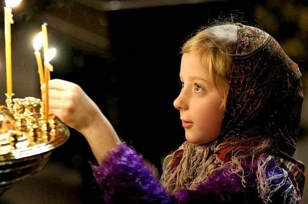 Ребенок ставит свечку в церкви