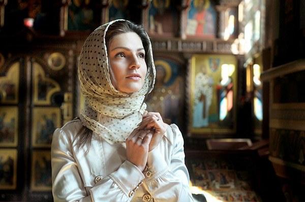 Девушка в храме молится Богу