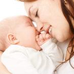 Мама улыбается новорожденному малышу