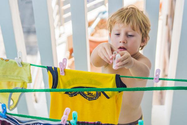 Мальчик помогает развешивать белье