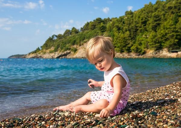 Ребенок играет на пляже Черногории