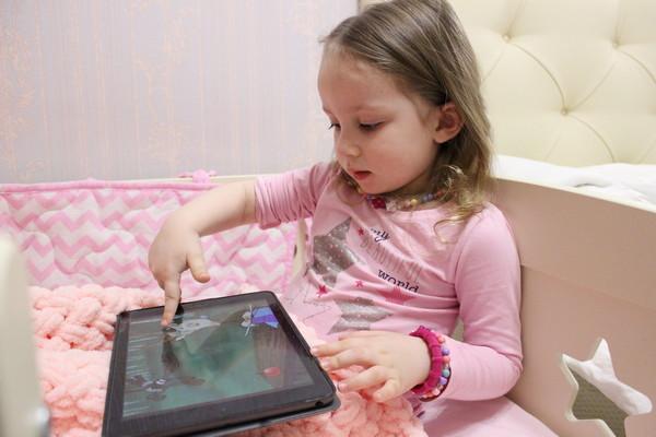Ребенок смотрит мультик на планшете